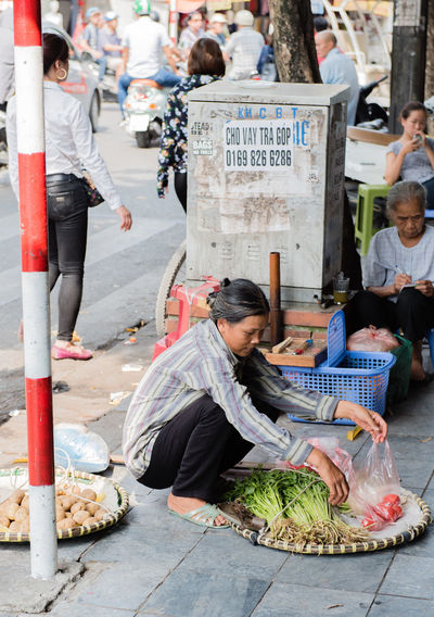 Vietnam, Hanoi - October 21, 2016: Vietnamese street vendors act and sell their vegetables and fruit products in Hanoi, Vietnam Adult Adults Only Assistants Baskets Bicycle Concept Day Fruit Hanoi Vietnam  Huế Outdoors People Street Shop Vegetable Market Vegetables Vendors Vietnam Vietnamese Woman ,