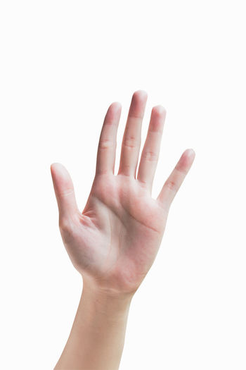 Close-up of cropped hand showing stop gesture over white background