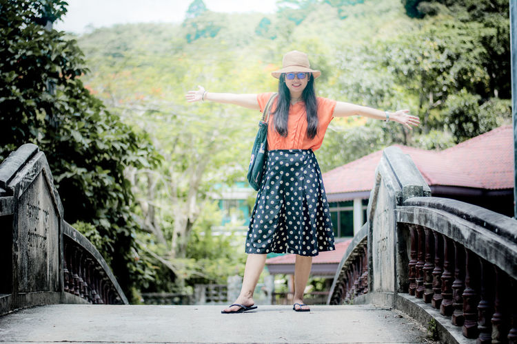 Portrait of young woman with arms outstretched standing on bridge against trees