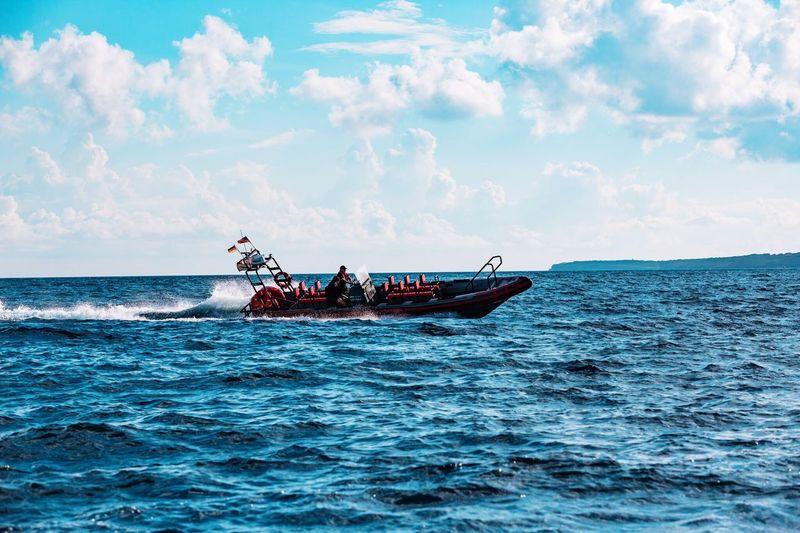Speedboat on sea against cloudy sky