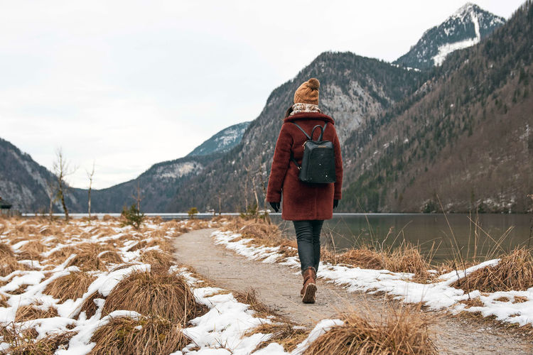 Young woman walking on a path by a lake. winter, snow, cold weather.