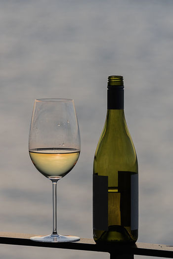 Close-up of wineglass with bottle on railing