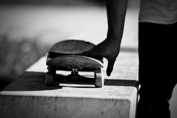 Cropped image of man with skateboard on retaining wall