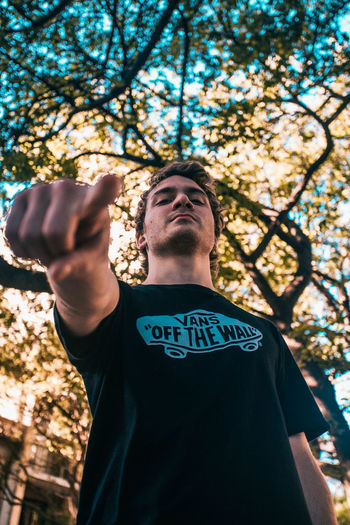 Low angle view of man standing against tree