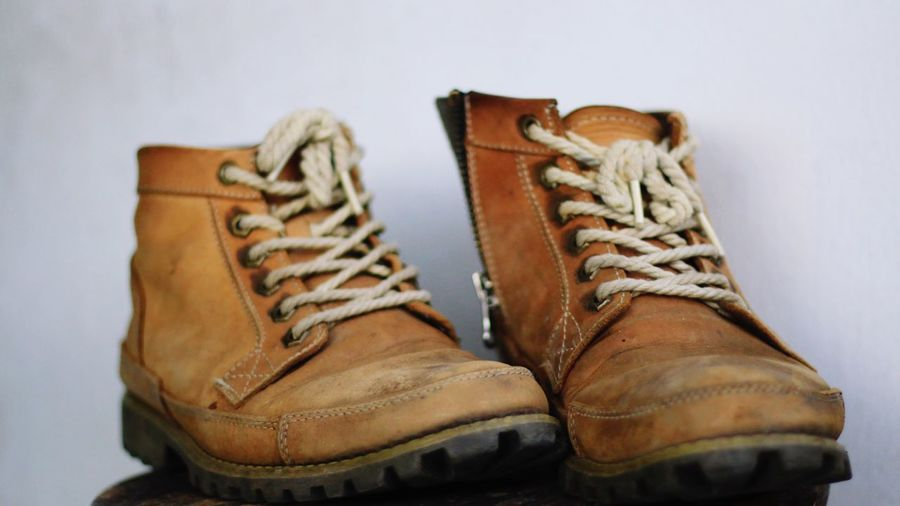 Close-up of old shoes against gray background