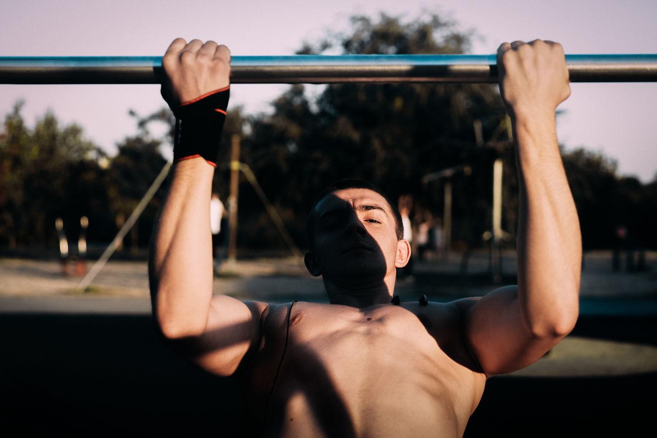 Shirtless man exercising at park