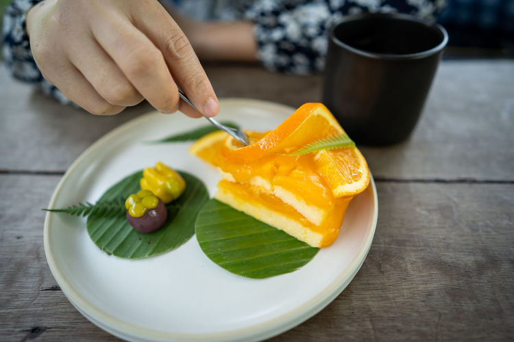 Close-up of hand holding fruits in plate on table
