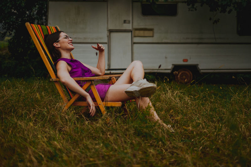 Smiling Woman Sitting On Chair Over Field