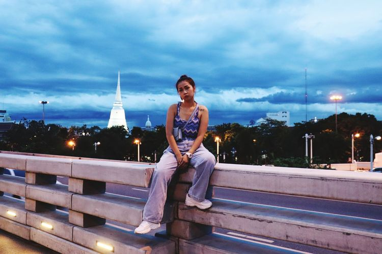 Portrait of woman sitting on railing against sky in city