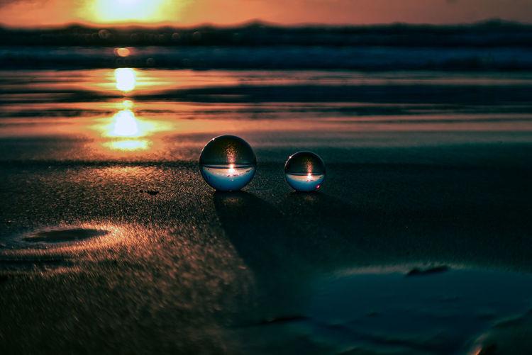 Close-up of sunglasses on beach against sunset sky