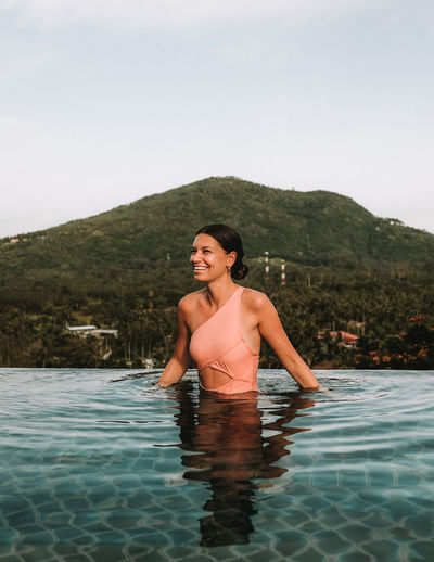 Happy young woman in swimming pool Mountain Brunette Model Ko Samui Thailand Resort Pool Beautiful Woman Laughing Girl Woman Outdoors Hairstyle Vacations Swimming Pool Happiness Young Adult Portrait Smiling Lifestyles Waterfront Leisure Activity Sky Water One Person