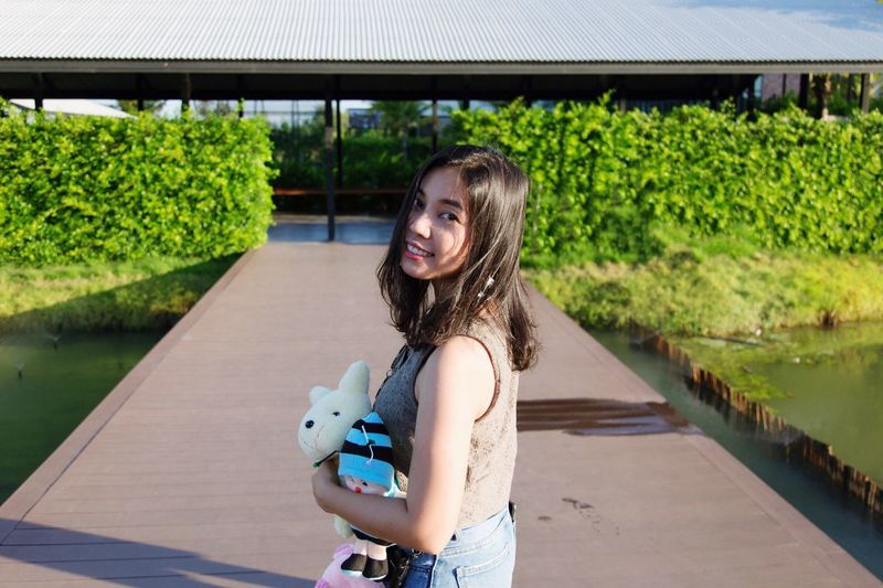 Portrait of smiling woman holding stuffed toy while standing outdoors