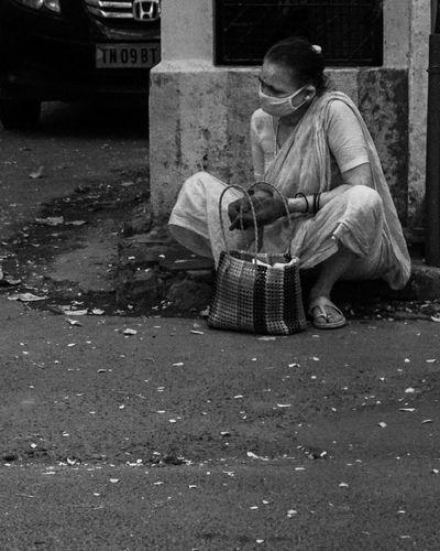 Man sitting on street in city