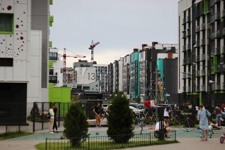 People on city buildings against sky