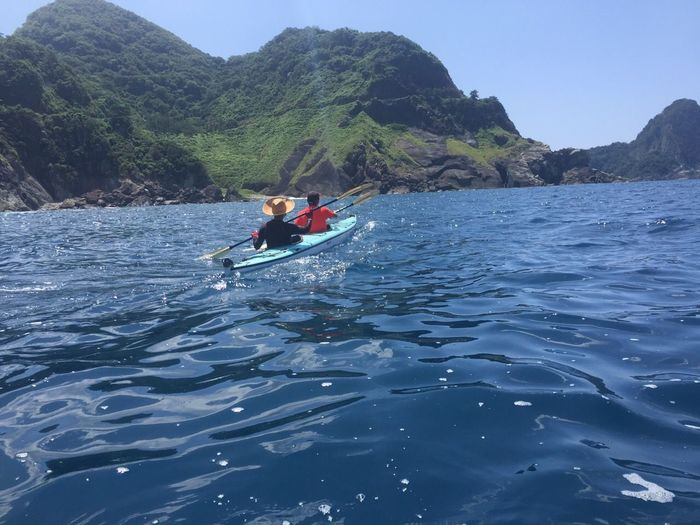 Rear View Of People Kayaking Over Sea By Mountains Against Clear Sky