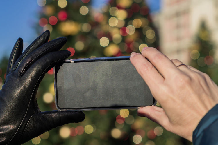 Cropped hand of woman holding smart phone standing outdoors