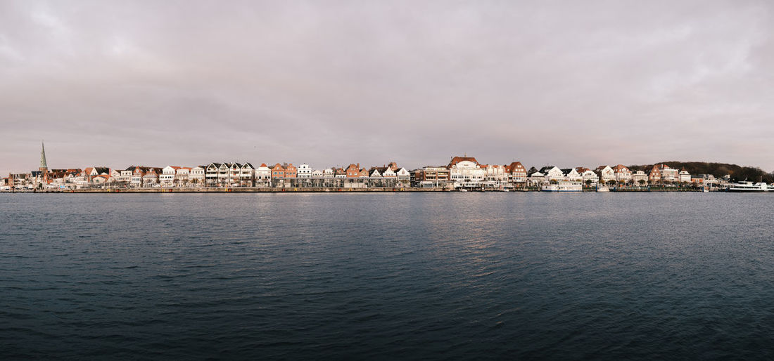 View of buildings by sea against cloudy sky