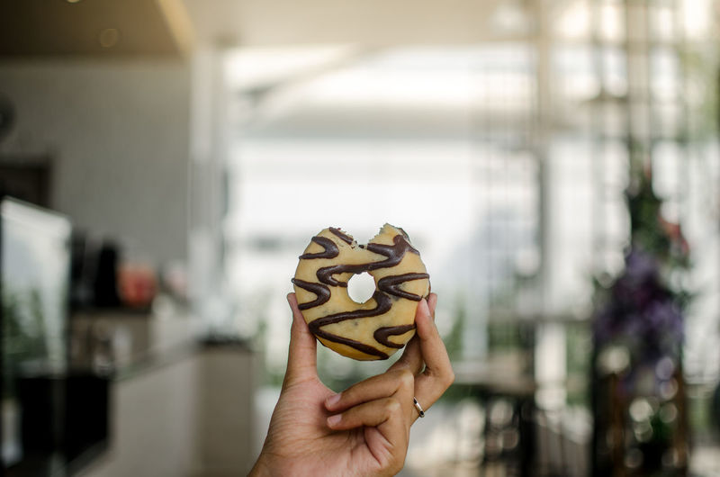 Cropped Hand Of Woman Holding Donut