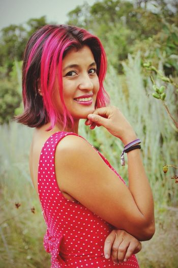 Portrait Of Smiling Woman With Pink Hair Standing On Field