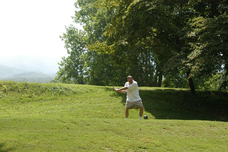 Man playing golf on grassy field against trees