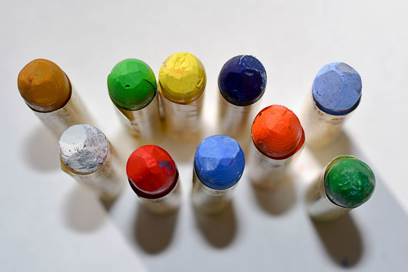 High angle view of multi colored pencils over white background