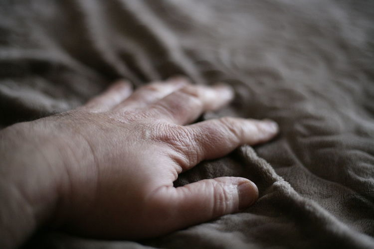 Close-up of hand on bed