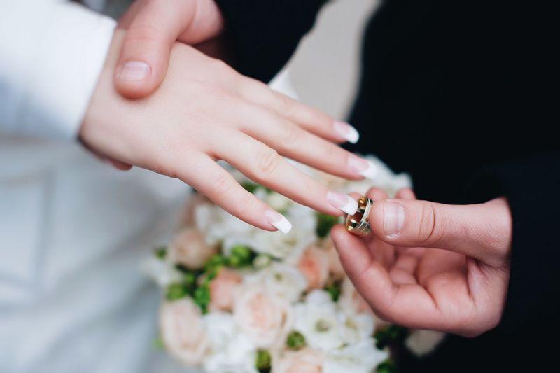 Groom putting ring in finger of bride