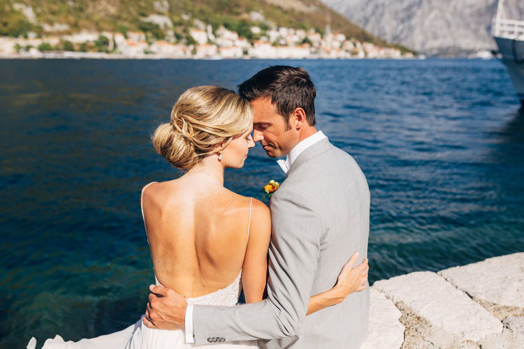 Rear view of couple embracing while sitting against sea