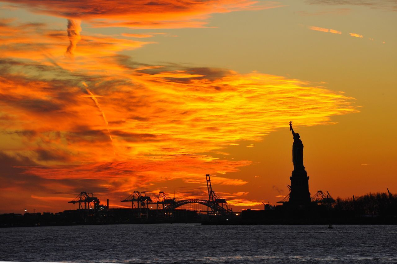 sunset, sky, cloud - sky, water, orange color, architecture, sculpture, statue, travel destinations, silhouette, nature, travel, sea, female likeness, human representation, waterfront, tourism, representation, no people, outdoors, freedom