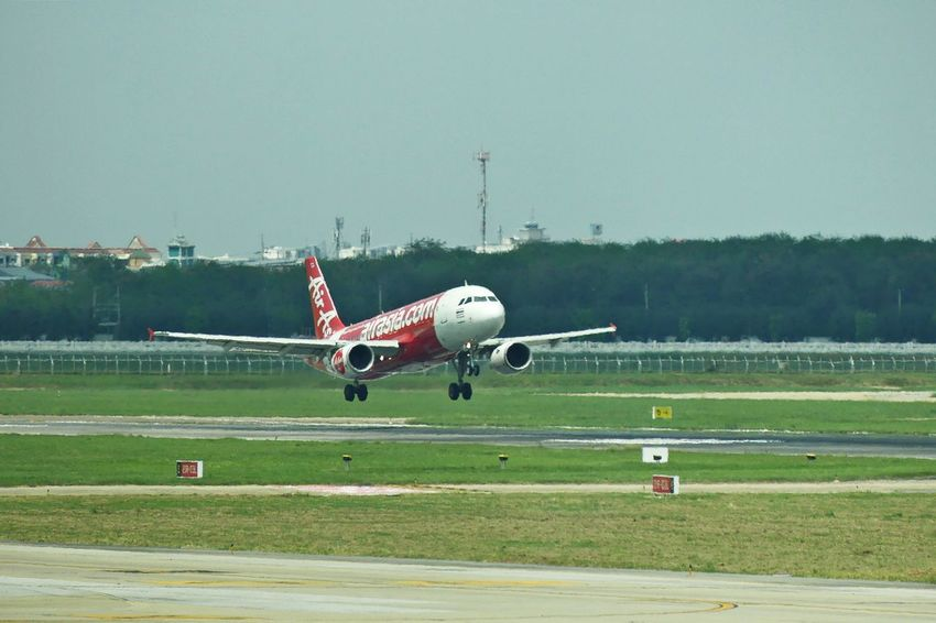 Bangkok, Thailand - April 14,2017 : Air asia Landing on runway airport at Don Mueang International Airport on April 14, 2017. Air asia is a Thai low-cost airline. Air Asia Air Vehicle Airfield Airplane Airport Airport Runway Airport Terminal Clear Sky Day Flying Grass Journey Landing Landing - Touching Down Landing Plane Mid-air Mode Of Transport No People Outdoors Runway Sky Transportation Travel รันเวย์ สนามบินดอนเมือง
