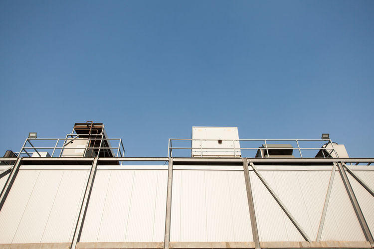 view from below of factory roof elements material Sky Architecture Low Angle View Built Structure Building Exterior Clear Sky Copy Space Day Blue Sunlight Building No People Industry Outdoors Metal Factory Corrugated Sunny Industrial System Environment Technology Architecture Roof Air Conditioner