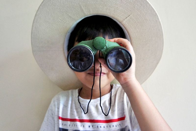 Close-Up Of Boy Looking Through Binoculars Against White Background