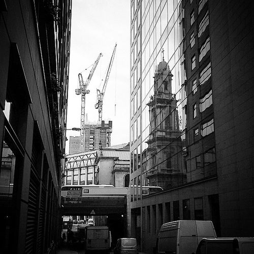 Chancery Lane area, London. The most transient City.. the 18th century church reflected in the 21st century glass building.. the cranes ahead building another new srutcture, the 19th century bridge ahead supporting the road carrying classic 1960's London Bus one way and the delivery truck the other. . The road underneath with the traffic rushing past....London a city constantly on the move...Fantastic Bandw Londoninblackandwhite Chancerylane London Londonsky Londonlife Londonview England English Britain British Uk Unitedkingdom GB