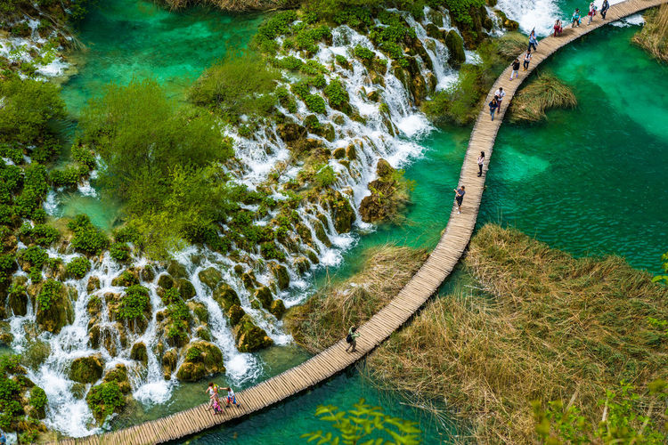 High angle view of people walking on boardwalk over water at plitvice lakes national park