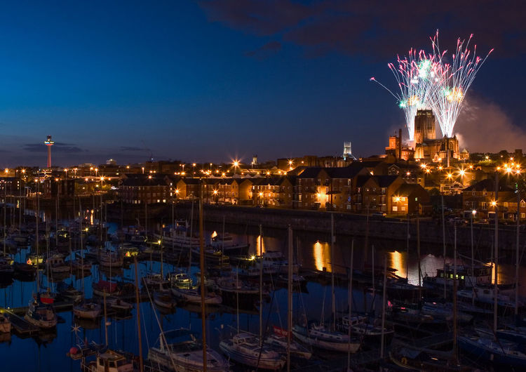 Firework display, harbor, and illuminated city at night