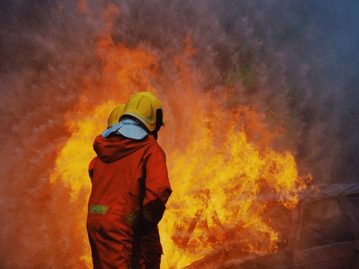 Burning Fire Fire - Natural Phenomenon Heat - Temperature Flame Accidents And Disasters Firefighter One Person Men Nature Real People Rear View Three Quarter Length Occupation Helmet Standing Protection Warning Sign Sign Clothing Outdoors Rescue Worker