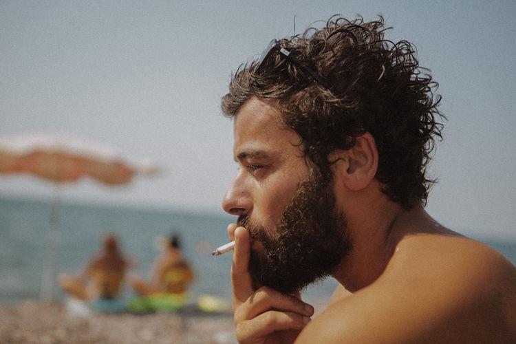 Close-Up Of Shirtless Man Smoking Cigarette At Beach