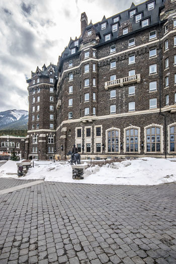 Banff  Banff National Park  Banff Springs Hotel Banff Alberta Mountain View Apartment Architecture Building Building Exterior Built Structure City Cloud - Sky Cobblestone Cold Temperature Day Footpath Nature No People Outdoors Residential District Sky Snow Street Transportation Winter
