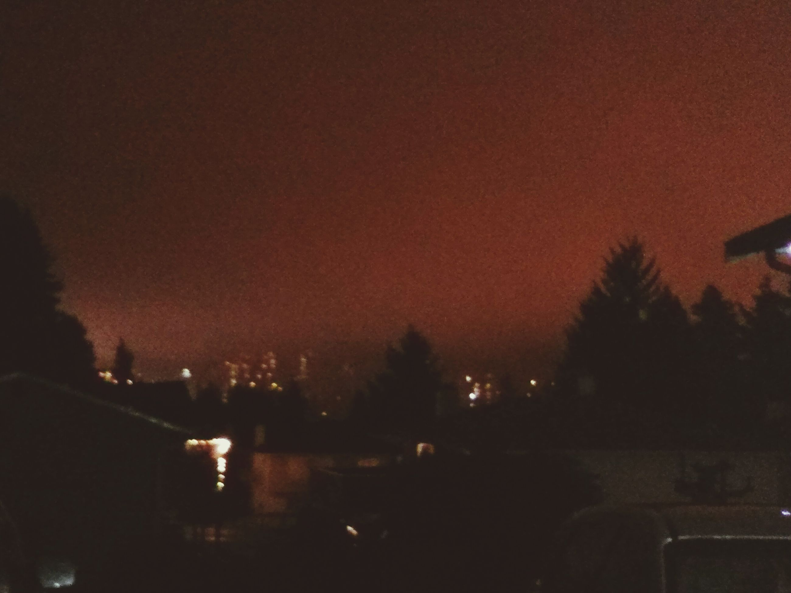 illuminated, sunset, silhouette, car, night, sky, transportation, land vehicle, dusk, building exterior, tree, mode of transport, street, street light, dark, city, built structure, road, architecture, outdoors