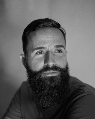 Man with long beard looking away against gray background