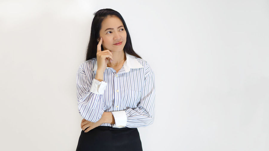 Businesswoman Contemplating While Standing Against White Background