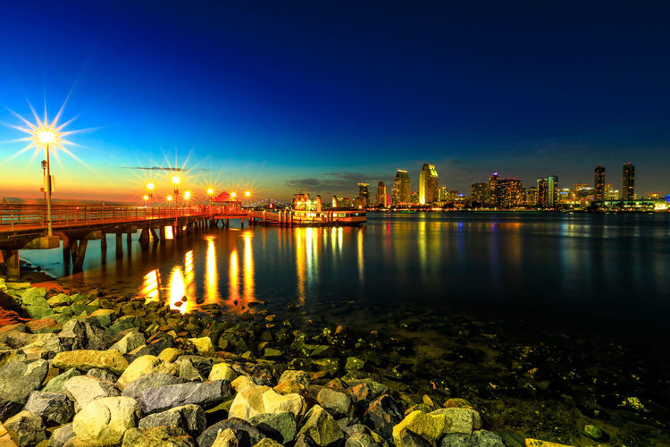 Panoramic landscape of San Diego skyline with illuminated skyscrapers reflecting in San Diego Bay at twilight. Districts of Waterfront Marina skyline and urban downtown cityscape at sunset light. Coronado Coronado Beach Coronado Island Sea Beach San Diego California United States America American Skyline Seascape Cityscape Sun Dock Port Holiday Vacations Sunset Night Pier Architecture Built Structure Water City Illuminated Building Exterior Sky Reflection Nature Building Travel Destinations No People Bridge Connection River Urban Skyline Bridge - Man Made Structure Landscape Office Building Exterior Outdoors Skyscraper
