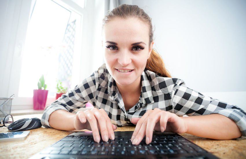 Casual Clothing Chat Chatting Confidence  Diminishing Perspective Domestic Life Focus On Foreground Front View Home Home Work Indoors  Laptop Laptop Keyboard Laptop Work Lifestyles Looking At Camera Person Portrait Relaxation Sitting Woman Portrait Work Young Adult Young Women