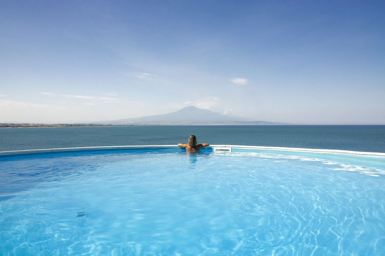 Adult woman relaxing in infinity pool looking at horizon with mount etna