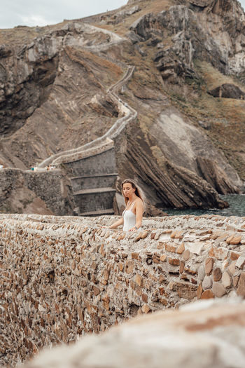 Young woman standing by stone wall