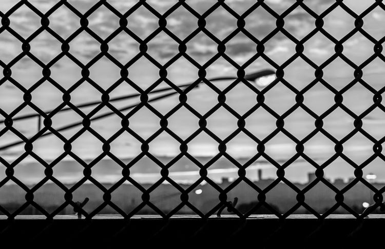 Behind the cage Abstract Colorful Background Abstract Nature Abstract Photography Blackandwhite Bw Chainlink Chainlink Fence Chainlink Gate Colorful Sky Complex Complexity Industrial Landscapes Juxtaposition Metal Mothernature Orange Sky Outdoors Street Lamp Sunbeam Sunrise Sunrise And Clouds Symmetrical Symmetry Urban Geometry Urbanexploration