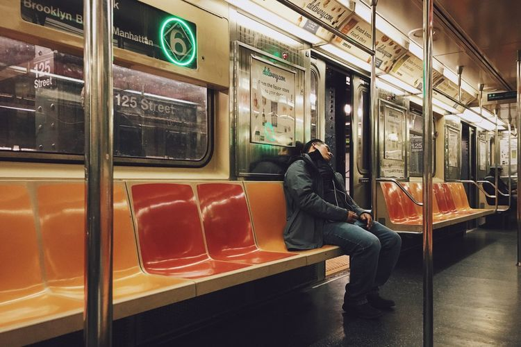 Rear view of man sitting in train