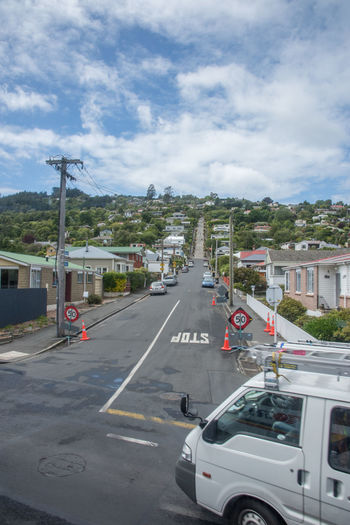 Dunedin,Otago,New Zealand-December 12,2016: Baldwin Street in the North East Valley, the Guiness world record holder for steepest road in the world, in Dunedin, New Zealand Baldwin Diminshing Perspective Dunedin Famous Guiness World Records North East Valley Residential  Road Transportation Tree Architecture Development Greenery Housing Neighborhood New Zealand Otago Road Marking Roadway Steep Steepest Street Suburban Suburbia Van