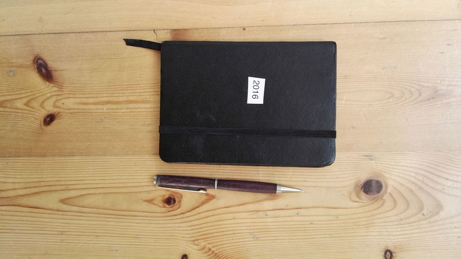Directly above shot of 2016 diary by pen on wooden table