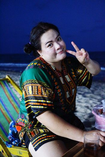 Portrait of woman showing peace sign while sitting on chair at beach during dusk